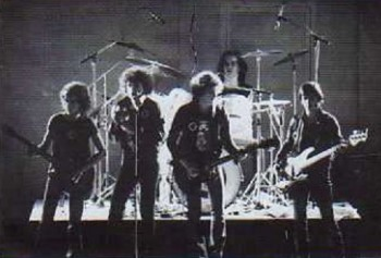 """8 NOVEMBRE 1979 : CACHE TA JOIE A SAINT-ETIENNE ! Créé de toutes pièces pour un festival en octobre 1975, Factory nous vient de Givors, citée ouvrière entre Lyon et Saint-Etienne. Le groupe ne joue alors que des reprises des Rolling Stones et de Chuck Berry. Le succès les pousse à continuer. Et Givors lui fera un triomphe un an plus tard. Premier album, Black Stamp, en septembre 1977 : Factory et son leader charismatique Yves Matrat chantent alors en anglais. Le second album contient en lui le mythe Factory : en français désormais, il est le fruit de la collaboration entre notre groupe et l'écrivain et scénariste Jean-Patrick Manchette qui propose à Factory de composer et d'assurer la partie musicale de """"Cache ta joie"""", la pièce de théàtre qu'il est en train de monter avec la Comédie de Saint-Etienne. Le second album de Factory portera ce titre et sera un grand succès. Factory part en tournée avec la Comédie de Saint-Etienne pour cette pièce de théâtre/concert. La première se déroule le 8 novembre 1979 à la salle des Mutilés de Saint-Etienne et restera dans les annales de toute une ville, de toute une jeunesse."""