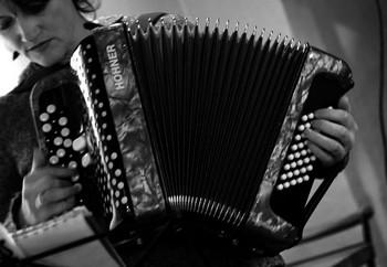 MAGALI FOURNIER, IMPERTINENTE ACCORDÉONISTE   Magali, c'est la jolie surprise de la soirée. Cette chanteuse autodidacte, qui a repris la chanson, sa passion de jeunesse, avec l'accordéon découvert à 15 ans, après avoir élevé ses enfants, se produit en café concert sur la région. Elle figurait d'ailleurs dans la programmation de l'Off du Festival de chanson française d'Aix où je n'avais pu me rendre. Un petit bout de femme dans sa robe fleurie, plantée avec aplomb devant ce public impressionnant quand on a l'habitude des petits lieux. Elle continue la tradition des chanteuses des rues avec une voix claire est bien posée de petite fille, une personnalité rebelle bien affirmée, et écrit et compose ses chansons. Elle nous avoue être une mauvaise fille, une mauvaise graine; se met dans la peau de la voleuse qui cambriolé son appartement. Fait l'inventaire des hommes qui pourraient être l'élu, comme Arno le fait avec Lola, Carla, Elga, Olga ou Cinderella, sans trouver la perle rare. Chansons sur les relations amoureuses, la fête de vivre, neuf titres en tout. Et termine par une J'ai peur qui fait penser à celle de Leprest, bien que sur un rythme entraînant (elle y a peur du vide, du noir, de tout, de rien, de Marine, des pompiers, de vivre…mais n'a plus peur dans ses bras) De la génération de ces chanteuses alliant charme et caractère.