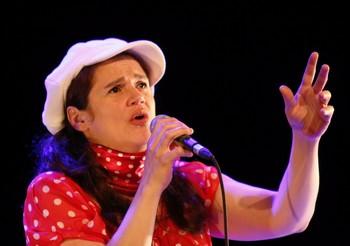 SANDRINE CABADI : « C'EST BEAU COMME CABADI ! »   Y'a pas à dire : ce que nous avons dit d'elle il y a peu sur NosEnchanteurs, à l'occasion de la sortie de son nouvel album Qui êtes-vous ?, nous le confirmons, mot pour mot. Avec, plus éclatante encore, la voix de Sandrine Cabadi : un bijou ! (écoutez Je suis jalouse, vous la jalouserez). De part et d'autre, un pianiste-accordéonniste (Christophe Barennes) et un violoniste (Charles Dubrez) : beau duo, tant qu'on regrette un peu que la chanteuse n'en profite pas pour se libérer de son propre clavier qui fait écran entre elle et le public, qui la rend, malgré quelques louables efforts, trop statique. Qu'elle soit de pure création ou de reprises (elle aime partager ce qu'elle aime, La mémoire et la mer inclue), qu'elle lorgne sur la chanson réaliste (son Saint-Lazare de Bruant est d'une très grande justesse d'interprétation) ou qu'elle aille sur un registre proche de la (très bonne) variété, la chanson de Sandrine Cabadi gagnerait à conquérir l'espace scénique, le faire sien, le posséder charnellement. Pour cela, point besoin d'être raccord avec le visuel de la pochette du disque (les petits pois à la Bécaud et surtout la casquette à la Gavroche), le talent de cette chanteuse est tellement évident qu'il doit s'affranchir de tels repères. On nous a tellement gonflé avec des « chanteuses à voix » (je ne cite aucun nom, pas même celui de Ségara, de peur d'en blesser) au répertoire désespérant, que la promesse d'une Sandrine Cabadi est séduisante, entre toute alléchante. Il suffirait de presque rien...