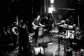 LE CONCERT . Liège, L'An Vert, 1er juin 2019   C'est en trio qu'Ivan Tirtiaux est venu présenter son nouvel album aux Liégeois. S'accompagnant à la guitare – et en piano-solo pour un seul morceau - , il s'est excellemment entouré de Mathieu Verkaeren, maître imperturbable ès contrebasse, à la rythmique solide et rassurante, et de Nyllo Canela, percussionniste aussi fou que brésilien, sosie d'Eric Judor, qui assure le show derrière ses multiples instruments (tambourins, pandeiros, surdos et autres caxixis… On m'a soufflé les noms !). Sept des huit chansons de l'album nous ont été interprétées, mêlées aux titres plus anciens. Dans leur version scénique, elles gagnent en énergie ce qu'elles perdent en contemplation. Le grand Lustucru, par exemple, devient une berceuse effrayante dotée d'effets sonores amusants, tandis que Dans la poitrine, chantée d'une voix déformée sur un rythme tribal, voit sa dimension dramatique accentuée. Les chansons du 1er disque (Charlatan, La course du soleil, Présage…) se dopent quant à elles aux rythmes brésiliens, digne prolongation scénique de la douceur estivale qui régnait sur Liège ce soir-là. La complicité des trois comparses est palpable et le plaisir qu'ils prennent à se produire devant nous a vite gagné l'assemblée, qui ne s'est pas fait prier pour chanter en choeur le refrain de Pourquoi remettre à demain ? Ce fut le point d'orgue d'une belle soirée, où paroles et musiques ont fait jeu égal. On en redemande. (photo Lara Herbinia)
