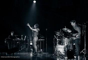 ILIA, LE CONCERT Liège, Cité-Miroir, 26 septembre 2019, Après le disque, le concert. Qui s'ouvre de la même manière : le lancinant Road song, le sautillant Il y a et l'envoûtant Charmeuse de tympans. Trois ambiances pour un bel aperçu de ce que sera la soirée. Sur scène, un batteur et un clavier accompagnent la chanteuse, rejoints par intermittence par un tromboniste. Des musiciens solides pour poser une ambiance propice à l'envolée de la salle dans les sphères de la poésie et de la transe musicale. Le chant d'Ilia est impeccable, bien entendu, malgré un rhume handicapant. Tout sourire, elle nous communique son bonheur d'être là, d'enfin partager ses chansons si longuement mûries, de nous emmener dans son univers à la fois tribal et sophistiqué. L'immense gamme vocale de l'artiste semble défiler (ça mélopée, ça jazze, ça scatte, ça groove), sans ostentation aucune pourtant. Et disons-le, l'émotion est davantage palpable que sur le disque, les petites imperfections scéniques ramenant davantage de vie. Avant de reprendre pour conclure son Il y a accompagnée par le public, Ilia nous offre a cappella une chanson qui l'accompagne depuis des années : La goutte d'eau de Nicole Rieu. Choix surprenant et évident à la fois, tant le timbre de la liégeoise semble façonné pour ce morceau et tant on devine qu'elle s'en sent proche. Ne se termine-t-il pas par : « J'ai quitté la route qu'on m'avait creusée / J'avais trop envie d'être écoutée » ??? (photo Bernard RIE photographies)